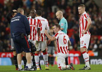 Stoke City's Glenn Whelan gets up from the pitch whilst  Ryan Shawcross looks on