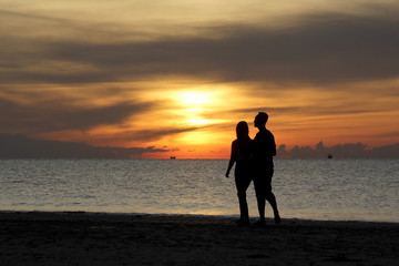 silhouette of couple walking on the beach