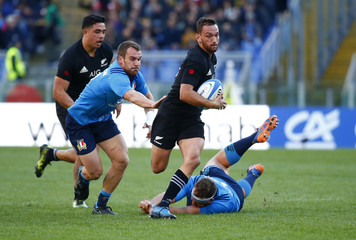 New Zealand's Aaron Cruden in action with Italy's Andrea Lovotti (R)