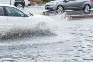 Splash by car as it goes through flood water after heavy rains of Harvey hurricane storm in Houston, Texas, US. Flooded city road with big puddle of water spray from the wheels of sedan car roaring by