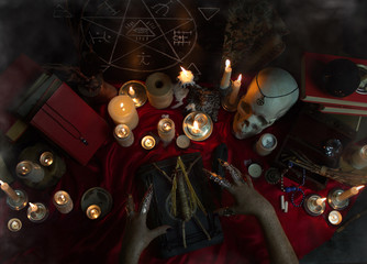 Witchcraft composition with witch's hands carrying out a ritual with Voodoo doll, candles, magic books, magic sphere, crystal, amulets and pentagram symbol. Halloween concept, black magic ritual.