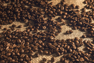 Roasted coffee beans on the fabric of the coffee bag.