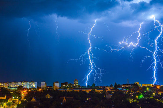 Lightning over the city in the night sky strikes the roof of the house