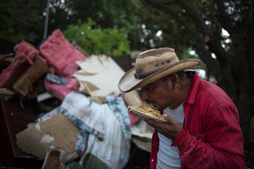 Man eats dinner without using utensils after clearing house of neighbor left flooded by Tropical Storm Harvey in Houston