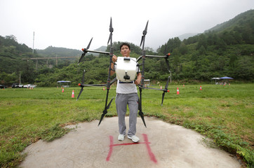A trainee holds an aerosol drone for calibration preparation before he learns to fly it at LTFY drone training school on the outskirts of Beijing
