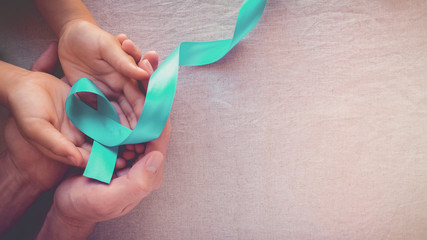Adult and child hands holding Teal Ribbon, toning panoramic banner background, Ovarian Cancer, cervical Cancer, Kidney Cancer and sexual assault awareness