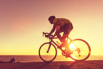 Road bike cyclist sports athlete biking outdoors silhouette near ocean. Professional triathlete riding bike on an open road to the sunset. Active healthy man sport lifestyle.