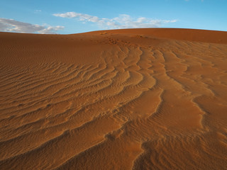 Beautiful natural pattern of rusty red sand dune with blue sky and white cloud background, Sossus, Namib Dessert