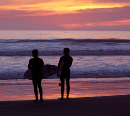 Surfers silhouetted with colorful sky and ocean background