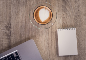 Hot coffee with heart make up on face of milk cream in glass cup on wooden table background, top view