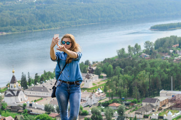 A young girl in blue clothes makes selfie on the background of a beautiful landscape