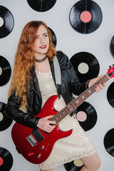 Sexy woman in a sequin dress, leather jacket and red lips. Disco style. Girl hipster playing the guitar.