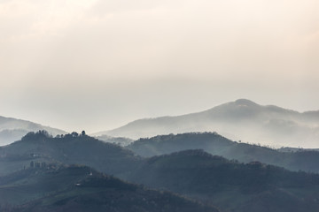 Green hills and trees in the foreground, mist and other hills and mountains in the background