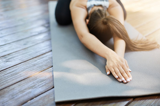 Close up of hands doing yoga or pilates laying on a grey mat in a temple or a backyard.