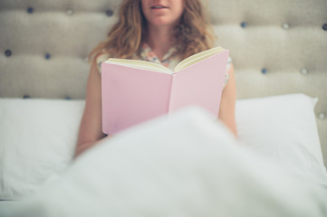 Woman reading pink book in bed