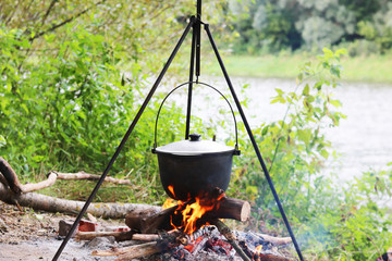 Cooking food in summer on nature at stake in cauldron