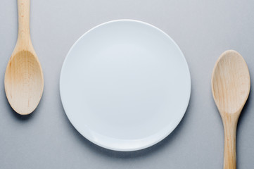 White plate on gray background. Mock up for menu or recipe. The concept of food or cooking