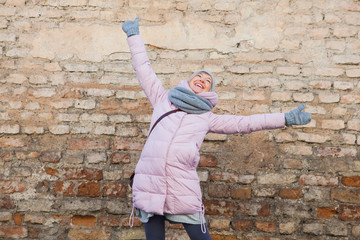 Young adult woman have fun on old brick wall background.