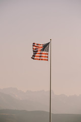 The American flag with  mountains