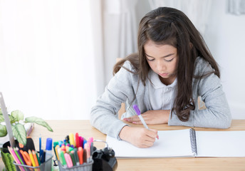 Cute Asia girl writing something in paper with colour pencils