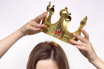 Woman girl holding above a head the golden crown. Leadership, success , queen.