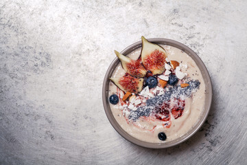 Blueberry banana smoothie bowl with figs and coconut on metal background. Flatlay with copy space