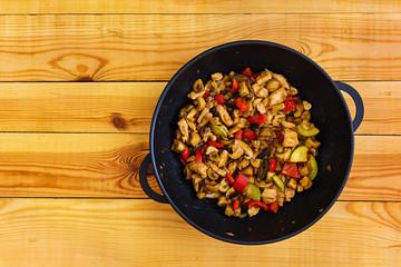 Stir fry chicken, zucchini and pepper in wok