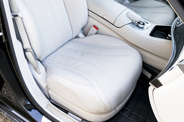 White leather interior of the luxury modern car. Leather comfortable white seats and multimedia. Steering wheel and dashboard. automatic gear stick.