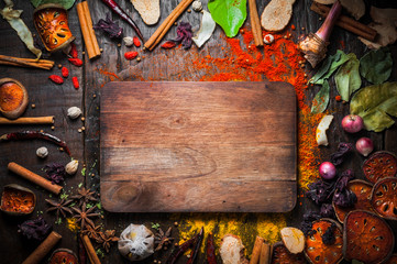Top view of old cutting board surrounded by spices herbs and ingredients for cooking on Rustic Wooden Table