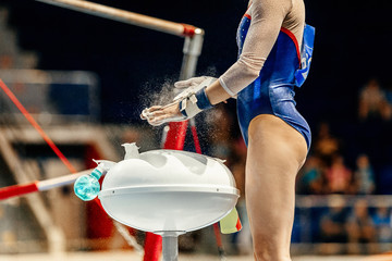 girl gymnast get ready in uneven bars. chalk in hand grips