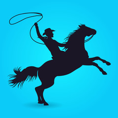 Silhouette of cowboy with lasso riding on horse