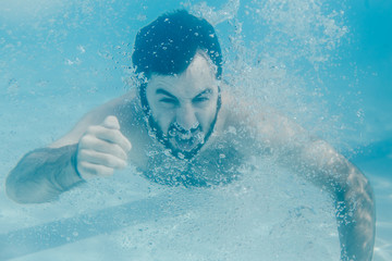 .Young man enjoying the pool on a sunny summer day. Taking photos at the swimmingpool so relaxed. Lifestyle portrait.