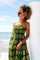 Attractive african model leaning against wall in a dress at beach
