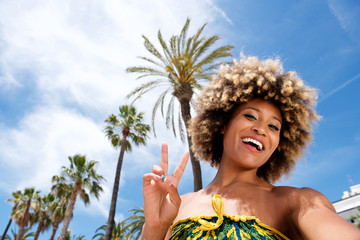 Beautiful young woman on vacation at the beach taking selfie and gesturing peace sign