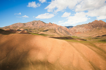 Mountain sandy ridges. View of the high mountains. Mountain valley during sunrise. Natural summer landscape.