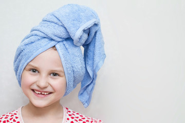 A little smiling girl with a blue towel on her head after bathing. Light background, copy space