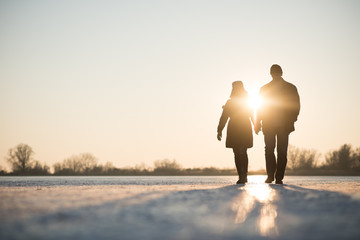 Couple walking through frozen lake as sun sets