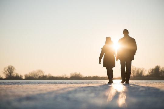 Couple walking through frozen lake as sun sets