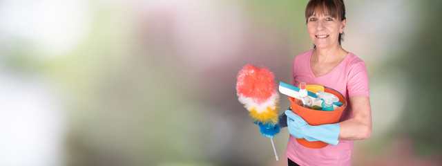 Housewife holding a duster and a bucket with cleaning equipment