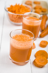 Carrot juice on a wooden table.