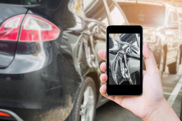 woman using mobile smart phone taking photo of the car crash damage accident