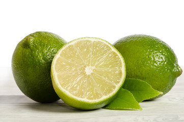 two lemons with half of  juicy lime on a wooden table