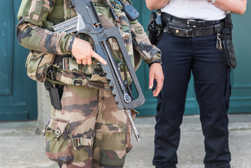 Close up of a French soldier with an automatic rifle, policeman in the background, security and emergency state concept