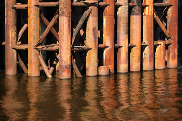 Rusty metal pipes in water, supports of old bridge construction