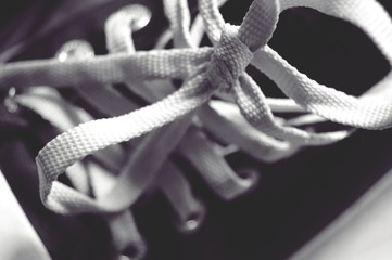 white shoelace tie on black sneakers shoe SELECTIVE FOCUS