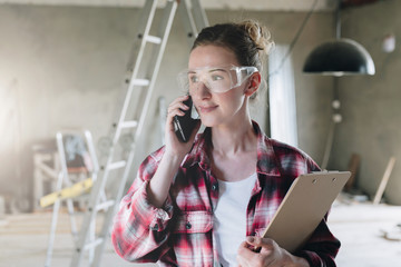 Portrait of businesswoman engineer, architect, designer.Girl standing,talking on cell phone and holding clipboard.