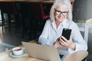 Smiling businesswoman is sitting at table in front of laptop and using smartphone. Pensioner freelancer works.