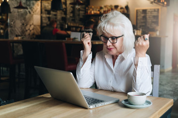 Happy business woman sitting at table in front of laptop, holding hands up and looking at monitor. Good news.