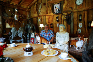 """Gary Blackburn, a 53-year-old tree surgeon from Lincolnshire, Britain, poses with a life-size model of Queen Elizabeth and two corgi dog mock-ups at """"Robin Hood's hut"""" of his British curiosities collection called """"Little Britain"""" in Linz-Kretzhaus"""
