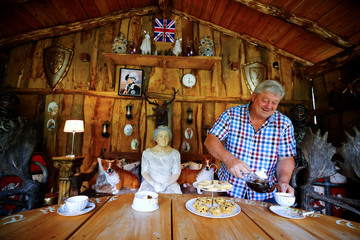 "Gary Blackburn, a 53-year-old tree surgeon from Lincolnshire, Britain, is having tea time with typical British short bread at ""Robin Hood's hut"" of his British curiosities collection called ""Little Britain"" in Linz-Kretzhaus"